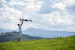 Happy father throws up a little son against a background of green forest, mountains and sky with clouds. Paternity friendship.  royalty free stock image