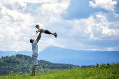 Happy father throws up a little son against a background of green forest, mountains and sky with clouds. Paternity friendship.  royalty free stock photo
