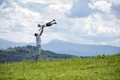 Happy father throws up a little son against a background of green forest, mountains and sky with clouds. Paternity friendship.  stock images