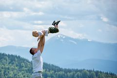 Happy father throws up a little son against a background of green forest, mountains and sky with clouds. Paternity friendship.  stock photos