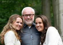 Happy father together with two smiling daughters. Close up portrait of a happy father together with two smiling daughters Royalty Free Stock Image