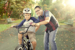 Happy father trains his son to ride a bike Royalty Free Stock Image