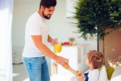 Happy father treats son with fresh juice and tasty dessert at summer patio garden Royalty Free Stock Images