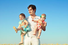 Happy father with two babies outdoors. Dad playing with daughters in sunny summer day. Father holding child. Portrait on blue sky. royalty free stock images