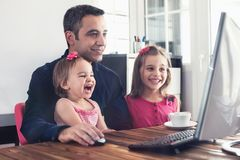 Happy Father and Two Child Daughters Watching on Computer royalty free stock images