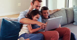 Happy father with two children using laptop. On sofa stock footage