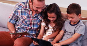 Happy father with two children using tablets. On sofa stock video