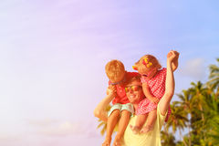Happy father with two kids on shoulders having fun Stock Photos