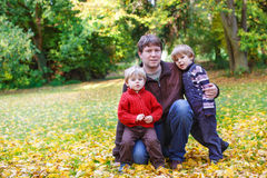 Happy father with two little sons having fun in autumn park. Royalty Free Stock Photo
