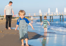 Happy father and two little sons having fun at beach vacation Stock Photography
