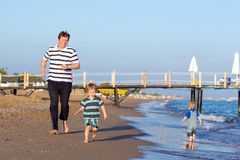 Happy father and two little sons having fun at beach vacation Stock Photo