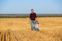 Happy father and two year old girl walking in harvested field Stock Images