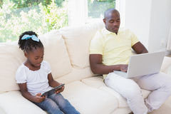 Happy father using laptop and her daughter using tablet on couch Royalty Free Stock Photography