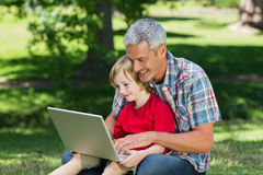 Happy father using laptop with his son. On a sunny day royalty free stock image