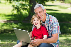 Happy father using laptop with his son. On a sunny day royalty free stock photography