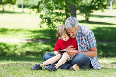 Happy father using tablet pc with his son Royalty Free Stock Photography