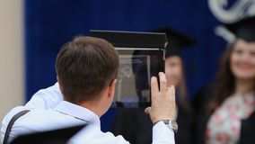 Happy father using tablet PC to take picture of daughter at graduation ceremony. Stock footage stock video footage