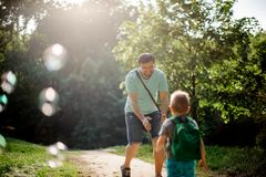 Happy father walking in the summer park with his little son. Happy father walking in the summer park and playing with soap bubbles with his little son stock photography