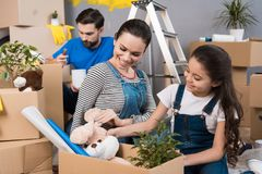 Happy father and wife and daughter sort things out from cardboard boxes in house they moved. Moving young family to new apartment Royalty Free Stock Photography