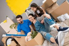 Happy father and wife and daughter sort things out from cardboard boxes in house they moved. royalty free stock images