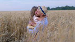 Happy fatherhood, little fair kid girl smiles having fun and hugging her beloved young father during outing in yellow stock footage