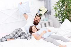 Happy fatherhood. Man bearded hipster with childish hairstyle colorful ponytails and daughter in pajamas. Guy and girl stock photo
