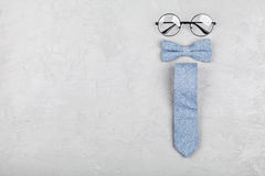 Happy Fathers Day background with glasses, necktie and bowtie on stone table top view in flat lay style. Royalty Free Stock Photo
