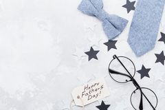 Happy Fathers Day background with greeting tag, glasses, necktie, bowtie and star confetti on table top view. Flat lay. stock photos