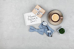Happy Fathers Day background with morning coffee cup, gift, glasses and bowtie on stone gray desk top view in flat lay style. Royalty Free Stock Image