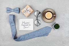 Happy Fathers Day background with morning coffee mug, gift, glasses, necktie and bowtie on stone table top view in flat lay style. Royalty Free Stock Images