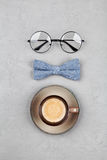 Happy Fathers Day background with morning coffee mug, glasses and bowtie on stone gray table top view in flat lay style. Happy Fathers Day background with Royalty Free Stock Images