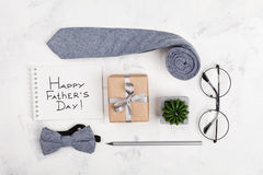 Happy Fathers Day background with notebook, gift, glasses, necktie and bowtie on light working desk top view in flat lay style. Stock Image
