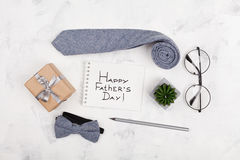 Happy Fathers Day background with notebook, gift, glasses, necktie and bowtie on white working desk top view in flat lay style. royalty free stock photography