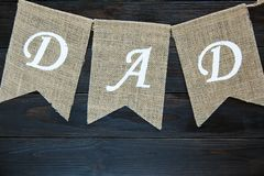 Happy Fathers day banner on the brown vintage wooden background. word Dad wriiten on the flags. royalty free stock images