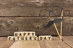Happy Fathers Day blocks with mustache and glasses against wood. Happy Fathers Day wooden blocks with mustache and glasses against a rustic wooden background stock photos
