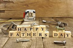 Happy Fathers Day blocks on rustic wood. Happy Fathers Day blocks with tools on a rustic wood background stock photography