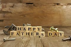 Happy Fathers Day blocks on rustic wood. Happy Fathers Day blocks with tools on a rustic wood background Royalty Free Stock Photography
