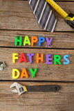 Happy fathers day blocks, tie, measuring tape and handtools on wooden plank. Close-up of happy fathers day blocks, tie, measuring tape and handtools on wooden stock photo