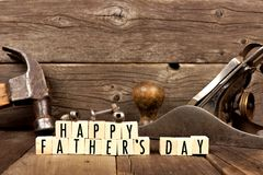 Happy Fathers Day blocks with tools in background against wood. Happy Fathers Day wooden blocks with vintage tools in the background against rustic wood Stock Image