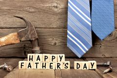 Happy Fathers Day blocks with tools and ties against wood royalty free stock image