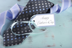 Happy Fathers Day blue tie with gift tag. On vintage aqua blue rustic shabby chic table with greeting and blue stripe ribbon royalty free stock photo