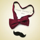 Happy fathers day. A bow tie forming a heart, a mustache and the sentence happy fathers day in a beige background, with a retro effect royalty free stock images