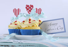 Happy Fathers Day bright and cheery red white and blue decorated cupcakes with heart toppers and gift tag. On vintage blue shabby chic background stock photography