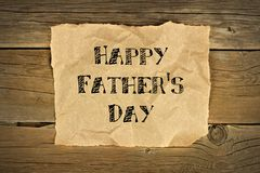 Happy Fathers Day on brown paper on rustic wood Royalty Free Stock Photos