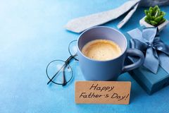 Happy Fathers Day card, cup of coffee, gift box and eyeglasses on blue table for breakfast. Stock Images