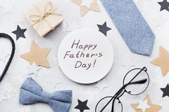 Happy Fathers Day card decorated bowtie, necktie, eyeglasses, gift box and stars on stone table top view in flat lay style.