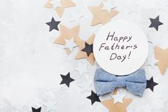 Happy Fathers Day card decorated bowtie and stars on stone table top view in flat lay style. Royalty Free Stock Image