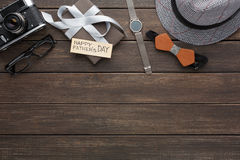 Happy Fathers Day card on rustic wood background. With border of present, watch, hat and other man things stock image