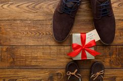 Happy Fathers Day card on rustic wood background. Happy Fathers Day card background on rustic wood with present, male and child shoes, copy space Royalty Free Stock Images