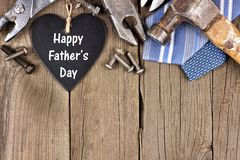 Happy Fathers Day chalkboard heart with top border on wood. Happy Fathers Day chalkboard heart with top border of tools and ties on a wooden background royalty free stock image